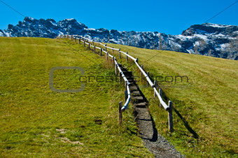 Dolomites mountain trail and fence on the lawn