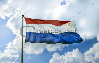 Waving flag of The Netherlands on the flagpole against cloudy bl
