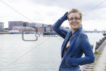 portrait of cute smiling girl against industrial and river backg