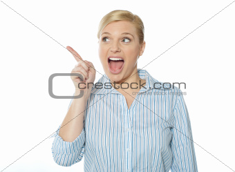 Excited female business executive pointing away