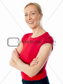 Smiling middle aged lady, poisng with folded arms