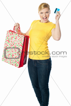 Happy shopaholic girl showing credit card