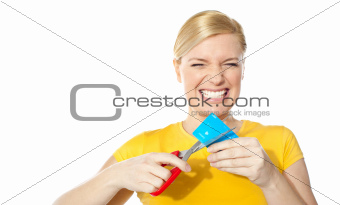 Woman grinding teeth while cutting her credit card