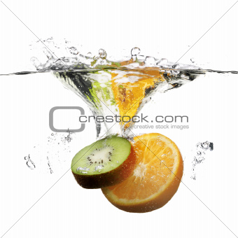 fruits dropped in water with splash on white