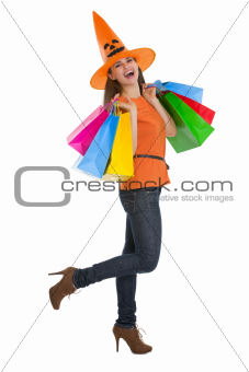 Smiling young woman in Halloween hat with shopping bags