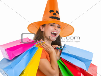 Happy young woman in Halloween hat with shopping bags