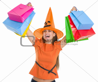 Smiling woman in Halloween hat rising up shopping bags