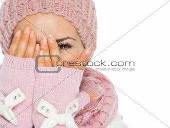 Woman in knit scarf, hat and mittens hiding behind hands