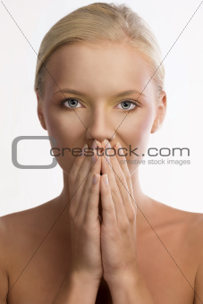 portrait of blonde girl with colored make-up and hands on the mo