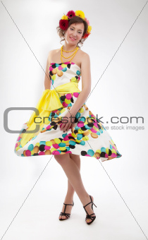 Graceful joyful young girl in colorful spring dress posing