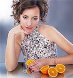 Lovely young girl with fresh halves of oranges sitting
