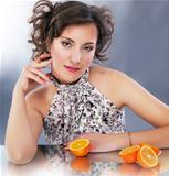 Young cute woman with citrus sitting