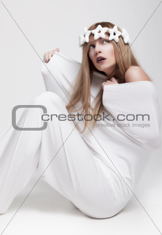Actress in theatrical pose sitting in white cloth studio shot