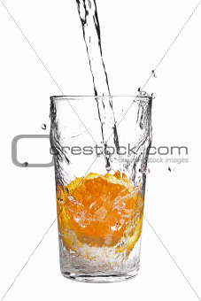 pouring water into glass with orange slice on white