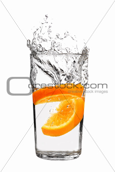 orange splashing into glass of water on white background