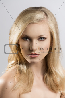 beauty portrait of pretty blonde girl looks in to the lens