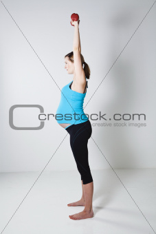 Pregnant woman exercising with dumbbells