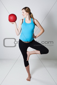 Pregnant woman exercising with exercise ball while balancing