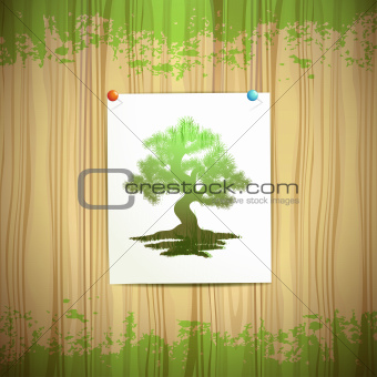 Green tree over sheet of paper