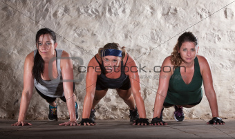 Three Women Do Push Ups in Boot Camp Workout