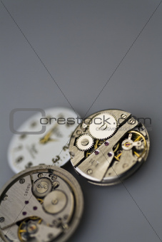Old metal mechanical clock with gear wheels on a gray background
