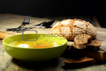 Chicken soup with poached egg .