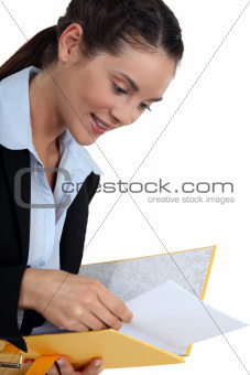 young businesswoman holding file looking pleased