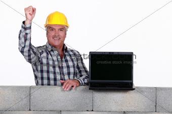 A mature mason with a laptop.