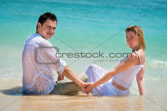 Young couple enjoying their holiday on the tropical beach 