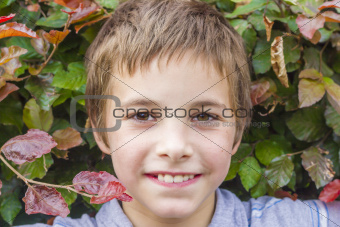 Portrait of smiling teenage boy at bush