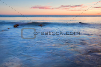 Beautiful sunset over Summer ocean with rocks and vibrant colors