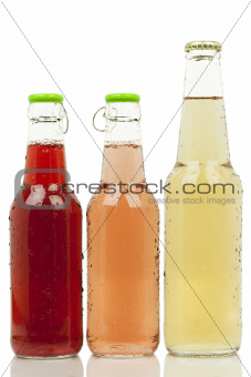 Three bottles with different colored drinks