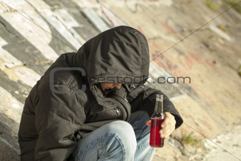 Boy with a bottle of hands sit under a bridge