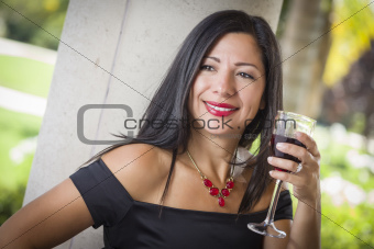 Attractive Hispanic Woman Portrait Outside Enjoying a Glass of Wine.