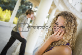 Woman Upset in the Foreground While Man Comtemplates in the Background