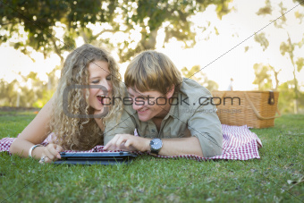 Playful Loving Couple Using a Touch Pad Computer at Their Picnic Outside.