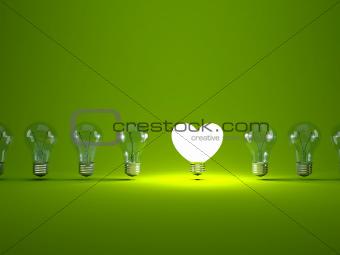 Heart shaped light bulb on green background