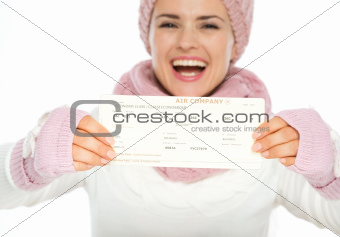 Closeup on air tickets in hand of woman in winter clothing