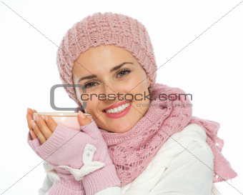 Happy woman in knit scarf, hat and mittens holding cup of tea
