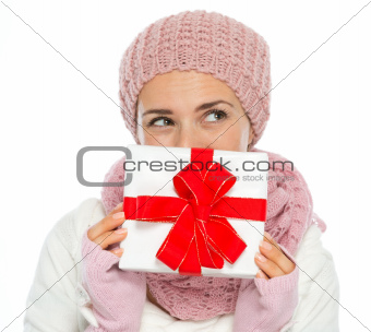 Thoughtful woman in knit winter clothing hiding behind Christmas present box