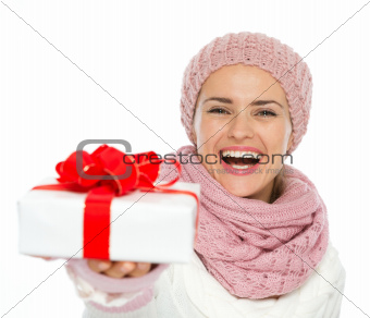 Happy woman in knit winter clothing giving Christmas present box