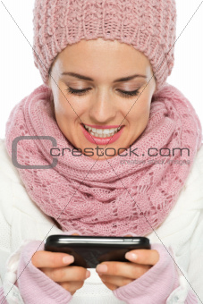 Happy woman in knit winter clothing writing text message