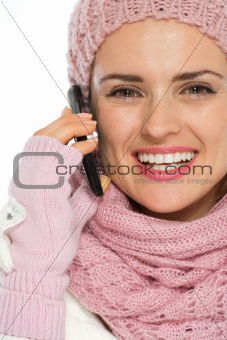 Smiling woman in knit winter clothing speaking mobile