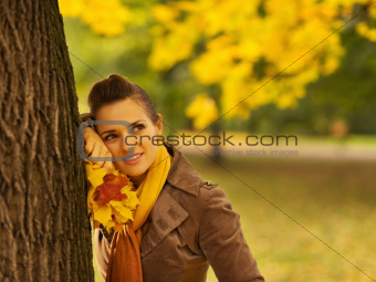 Thoughtful woman with fallen leaves leaning against tree