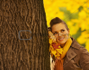 Dreaming woman with fallen leaves leaning against tree
