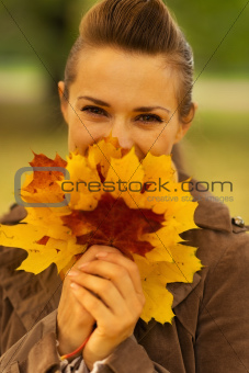 Happy woman hiding behind bunch of fallen leaves