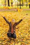 Happy woman squatting and throwing fallen leaves