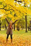 Happy woman throwing fallen leaves