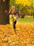 Cheerful woman kicking fallen leaves