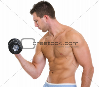 Strong male athlete raising dumbbell